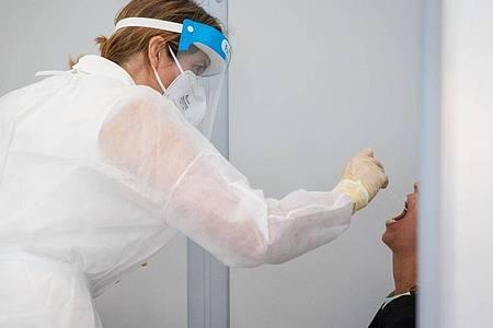 Eine Reisende wird im Corona-Testzentrum getestet. Foto: Christoph Schmidt/dpa