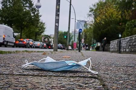 Ein Mund-Nasen-Schutz liegt auf dem Gehweg in Berlin-Friedrichshain. Foto: Annette Riedl/dpa