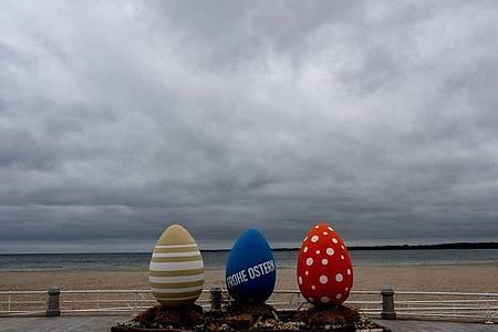 Bunt bemalte überdimensionale Ostereier stehen am wolkenverhangenen Strand von Travemünde. Foto: Axel Heimken/dpa