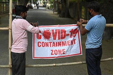 Städtische Arbeiter markieren im indischen Prayagraj ein zur Eindämmung der Pandemie abgeriegeltes Gebiet. Foto: Prabhat Kumar Verma/ZUMA Wire/dpa