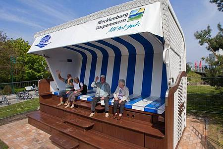 Die ersten Urlauber sitzen in dem größten Strandkorb der Welt in Heringsdorf. Foto: picture alliance / dpa