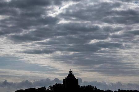 Wolken hängen über dem Leuchtturm auf Neuwerk. Foto: Daniel Bockwoldt/dpa