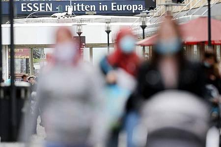 Passanten mit und ohne Mund-Nasen-Schutz gehen durch eine Einkaufsstraße in Essen. Foto: Roland Weihrauch/dpa