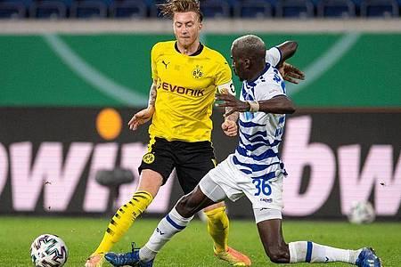 Marco Reus (l) vonBorussia Dortmund und Wilson Kamavuaka vom MSV Duisburg kämpfen um den Ball. Foto: Marius Becker/dpa