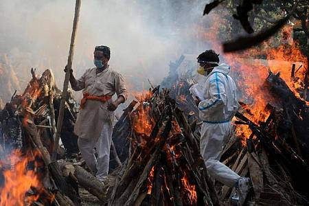 Neu Delhi: Angehörige neben brennenden Scheiterhaufen von Opfern, die an den Folgen einer Corona-Infektion gestorben sind. Foto: Naveen Sharma/SOPA/ZUMA/dpa
