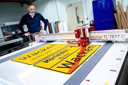 Michael Mazur, Abteilungsleiter Druckverfahren in der Fritz Lange GmbH, begutachtet den Zuschnitt einer Ortstafel von Wacken auf spezieller selbstklebender Folie. Foto: Hauke-Christian Dittrich/dpa