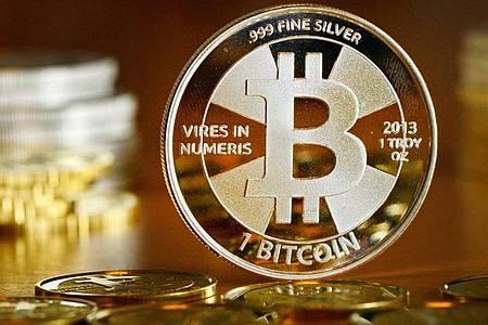 Das Bitcoin-Logo auf einer Münze. Foto: Jens Kalaene/zb/dpa