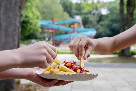 Pommes mit Ketchup und Mayo, natürlich im Freibad. Foto: Christoph Soeder/dpa