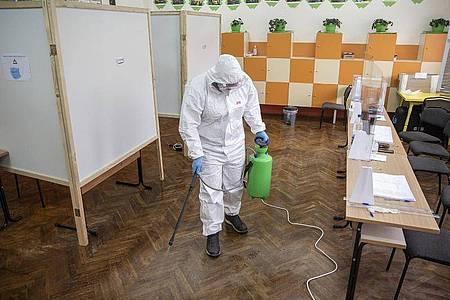 Abstimmung unter Corona-Bedingungen: Ein Arbeiter desinfiziert ein Wahllokal. Foto: Visar Kryeziu/AP/dpa
