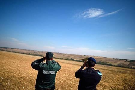 Zwei Beamte der europäischen Grenzschutzagentur Frontex aus Bulgarien (l) und den Niederlanden beobachten mit Ferngläsern die bulgarisch-türkische Grenze. Foto: Vassil Donev/epa/dpa