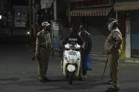 Polizisten kontrollieren einen Rollerfahrer während der nächtlichen Ausgangssperren. Foto: Channi Anand/AP/dpa