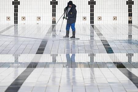 Ein Mitarbeiter reinigt ein Becken im Inselbad Untertürkheim in Stuttgart. Foto: Marijan Murat/dpa