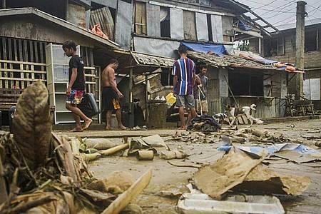 """Anwohner räumen Trümmer von den Überschwemmungen durch den Taifun """"Surigae"""" auf. Foto: Uncredited/AP/dpa"""