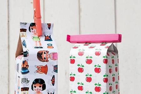 Mit eigenen Bildchen wird der Tetrapack zur dekorativen Box für Knabbereien. Foto: Claudia Schilling/AT Verlag/dpa-tmn