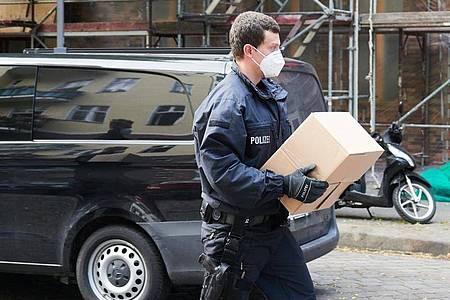 Ein Polizist trägt sichergestelltes Beweismaterial zu einem Auto. Foto: Paul Zinken/dpa-Zentralbild/dpa