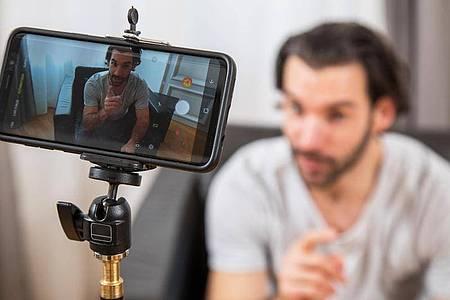 Ein Stativ mit Halterung reicht: Zum Start machen Smartphones ausreichend gute Videos. Foto: Christin Klose/dpa-tmn