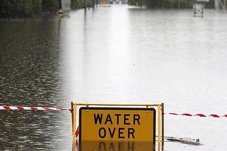 Ein Schild mit Warnhinweis auf einer überfluteten Straße bei Windsor. Tagelanger Starkregen hat im Osten Australiens die schlimmsten Überschwemmungen seit Jahrzehnten ausgelöst. Foto: Rick Rycroft/AP/dpa