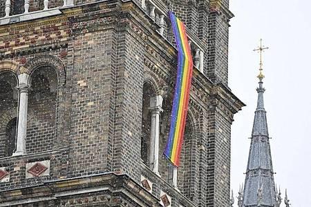 Eine Regenbogenfahne schmückt die Pfarrkirche Breitenfeld in Wien. Foto: Herbert Neubauer/APA/dpa
