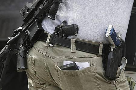 Eine Person mit mehreren Schusswaffen nimmt 2018 an einer Demonstration für das Recht, Waffen zu besitzen, teil. Foto: Genna Martin/seattlepi.com/AP/dpa
