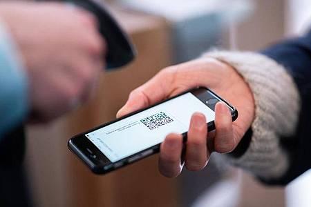 Eine Frau lässt am Eingang eines Corona-Schnelltest-Zentrums einen QR-Code auf ihrem Smartphone abscannen. Foto: Daniel Reinhardt/dpa