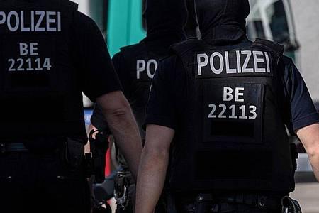 Polizisten gehen in Tempelhof vor einem Gebäude über die Straße. Foto: Paul Zinken/dpa/Aktuell