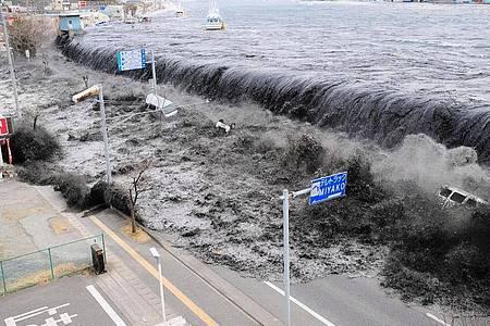 Meterhohe Wellen überfluteten vor uehn Jahren einen Deich in der Nähe der Mündung des Hei-Flusses. Vor zehn Jahren verursachten ein Erdbeben und ein Tsunami einen Super-GAU im Atomkraftwerk Fukushima. Foto: Aflo / Mainichi Newspaper/AFLO/EPA/dpa
