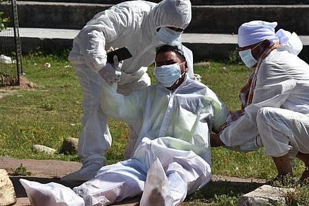 Kein Trost, kaum Hoffnung: Die Corona-Situation inIndien ist außer Kontrolle - ein Angehöriger einer infolge einer Covid-Erkrankung verstorbenen Frau bricht während der Einäscherung zusammen. Foto: Nazim Ali Khan/ZUMA Wire/dpa