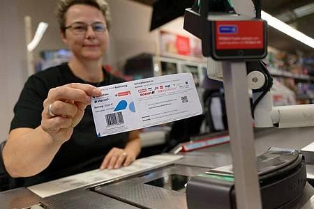 Eine Mitarbeiterin in einer Filiale des Einzelhändlers REWE hält ein Blatt mit einem Barcode in der Hand. Mit diesem Abschnitt sollen Bürger in Köln ihre Knöllchen künftig einfach an Supermarktkassen begleichen können. Foto: Henning Kaiser/dpa