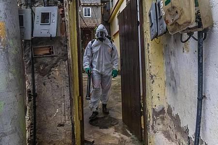 Ein Mann mit Schutzkleidung und einem Gerät zur Straßendesinfektion in einem Armenviertel von Rio de Janeiro. Foto: Ellan Lustosa/ZUMA Wire/dpa