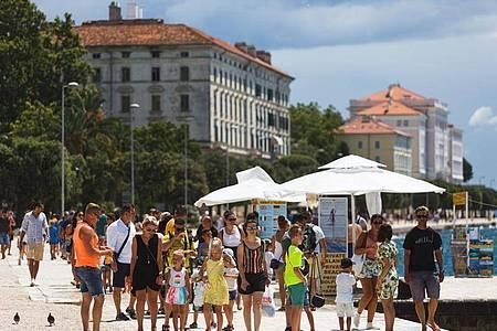 Touristen spazieren an der Uferpromenade in Zadar, Kroatien entlang. Die kroatische Tourismusbranche fürchtet eine weitreichende Reisewarnung der Bundesregierung. Foto: Marko Dimic/Pixsell/Xinhua/dpa