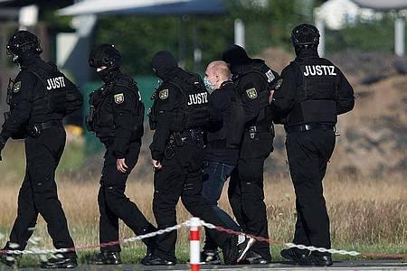 Der Angeklagte Stephan Balliet wird vor dem vierten Prozesstag von Justizbeamten aus dem Hubschrauber gebracht. Foto: Ronny Hartmann/dpa