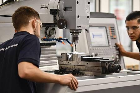 Die angehenden Industriemechaniker Noah Hecker und Mohammed Elosrouti (r.) kontrollieren die Bohrung eines Werkstücks an einer Fräsmaschine. Foto: Kirsten Neumann/dpa-tmn
