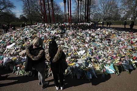 Zwei Frauen schauen sich die Blumen an, die für die getötete Sarah Everard im Clapham Common Park in London niedergelegt wurden. Foto: Yui Mok/PA Wire/dpa