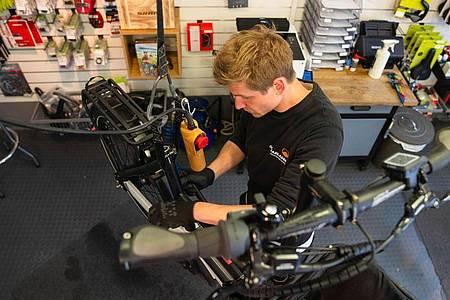 Kennt sich mit den Bauteilen von E-Bikes bestens aus: Stefan Borschert repariert die Pedale eines Lastenrads. Foto: Nicolas Armer/dpa-tmn