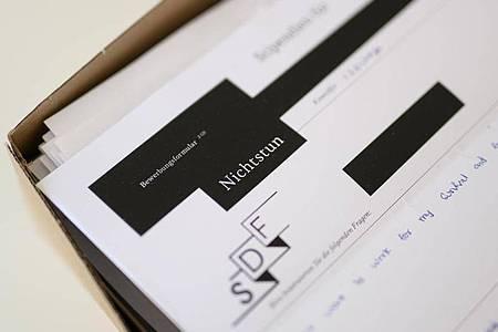 Ein Bewerbungsformulare für ein Stipendium für das Nichtstun liegen auf einem Stapel in einem Büro der HFBK. Foto: Daniel Reinhardt/dpa