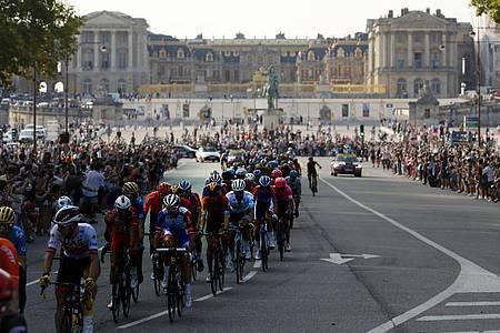 Das Fahrerfeld fährt am Schloss von Versailles vorbei. Foto: Christophe Ena/AP/dpa