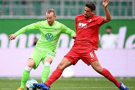 Wolfsburgs Maximilian Arnold (l) kämpft mit Augsburgs Rani Khedira um den Ball. Foto: Swen Pförtner/dpa