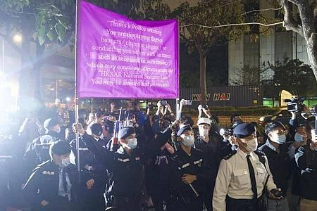 Polizisten hissen vor einem Gericht in Hongkong eine Warnflagge gegen die Unterstützer von 47 pro-demokratischen Aktivisten, die wegen angeblicher Verstöße gegen das neue Sicherheitsgesetz vorerst in Untersuchungshaft bleiben müssen. Foto: Vincent Yu/AP/dpa