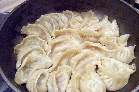 Wer es knusprig mag, kann die gekochten Jiaozi auch in der Pfanne anbraten. Foto: Ulrike Hecker/dpa-tmn