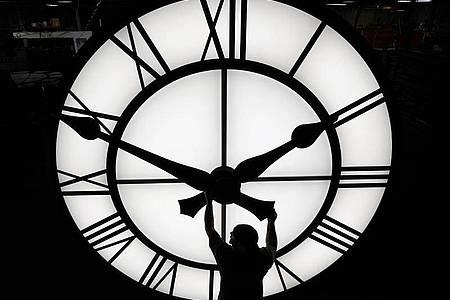 Ein Techniker bewegt die Uhrzeiger einer 500 kg schweren Uhr mit einem Durchmesser von mehr als 3,5 Metern. Foto: Elise Amendola/AP/dpa/Symbolbild