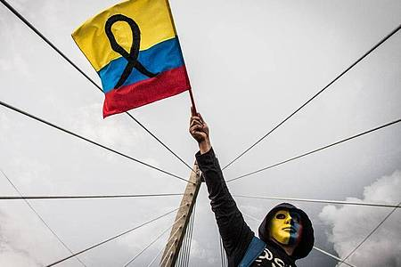 Ein maskierter Demonstrant schwenkt die kolumbianische Flagge. Foto: Juan Pablo Otalvaro M/dpa