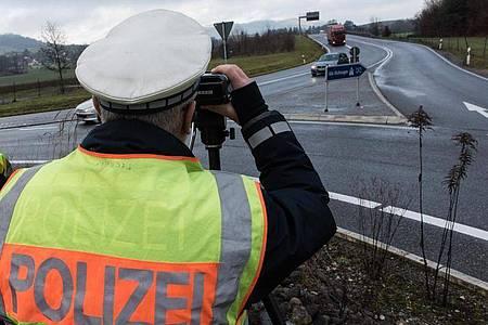 Ein Polizist misst die Geschwindigkeit passierender Autos. Die neuen Rgelungen des Bußgeldkatalogs für Verkehrssünder sind wegen eines Formfehlers zurzeit in Teilen außer Vollzug gesetzt. Foto: picture alliance / Patrick Seeger/dpa