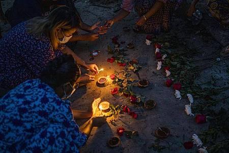 Frauen zünden während einer Zeremonie in Yangon Kerzen an, um den Opfern zu gedenken, die bei Massendemonstrationen gegen die Junta getötet wurden. Foto: Uncredited/AP/dpa