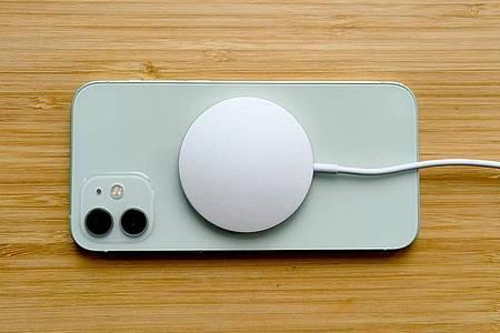 Das kreisrunde Drahtlos-Ladesystem Magsafe wird am Rücken des iPhone 12 magnetisch in der perfekten Ladeposition gehalten. Foto: Christoph Dernbach/dpa-tmn