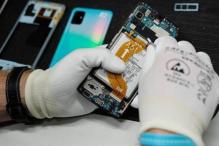 Reparatur eines Mobiltelefones in der Werkstatt der Komsa AG. Foto: Sebastian Willnow/dpa-Zentralbild/dpa