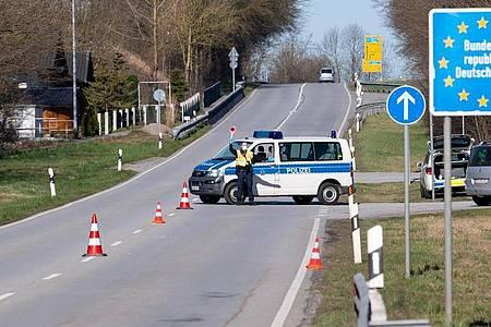 Polizisten an der Bundesstraße 512 in der Nähe von Neuhaus am Inn an einer Kontrollstelle an der Grenze zu Österreich. Foto: Sven Hoppe/dpa