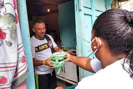 """Laryssa da Silva reicht einem Mann zwei Essenspakete in die Wohnung. Sie ist eine von 700 """"Straßenpräsidenten"""" in Paraisopolis. Foto: Caio Capicoré/G10 Favelas/Presidentes de Rua/dpa"""