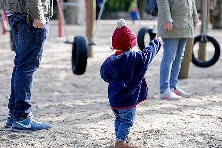 Ein Kind spielt mit seinen Eltern auf einem Spielplatz. Foto: Christoph Soeder/dpa