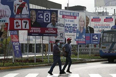 Wahlplakate der Kandidaten stehen an einer Straße in Lima. Foto: Martin Mejia/AP/dpa