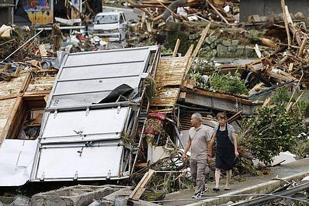 Ein Paar geht durch ein Trümmerfeld. Die Zahl der Todesopfer in den von schweren Unwettern heimgesuchten Überschwemmungsgebieten im Südwesten Japans ist weiter gestiegen. Foto: -/Kyodo News/AP/dpa